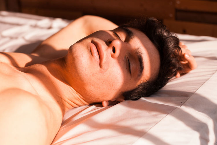 Sunlight falling on young man sleeping on bed