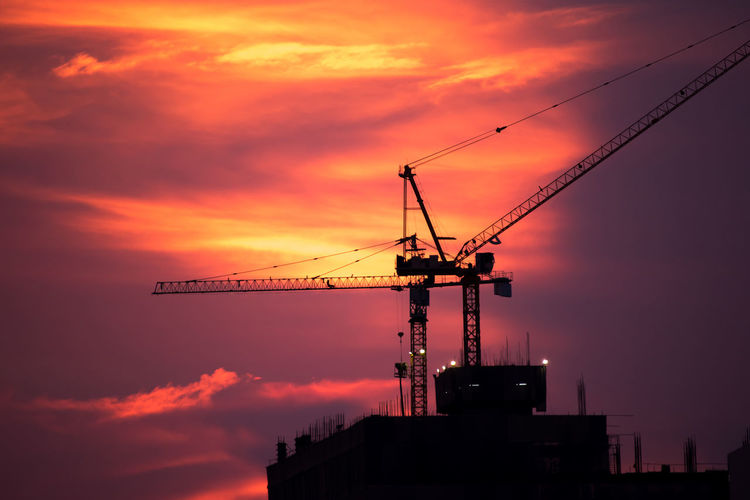 Low Angle View Of Silhouette Cranes Against Cloudy Sky During Sunset