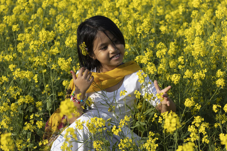 Smiling girl sitting amidst yellow flowers