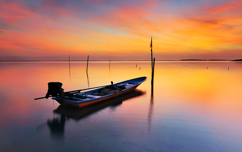 Silhouette boat moored on sea against sky during sunset