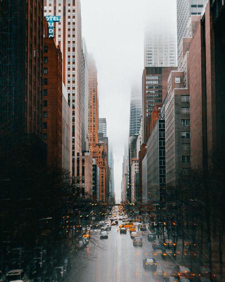 City street amidst buildings against sky during rainy season