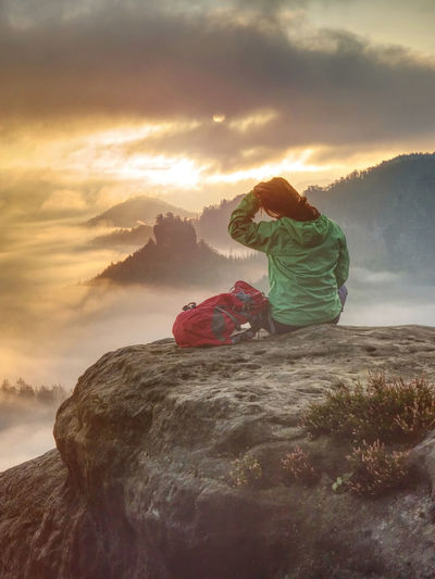 Woman just enjoying the life. beautiful girl backpacker sitting on top of the mountain and enjoy day