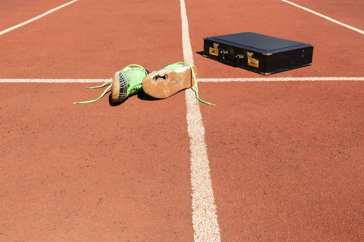 A briefcase and broken running shoes on a running track symbolizing competition and in business
