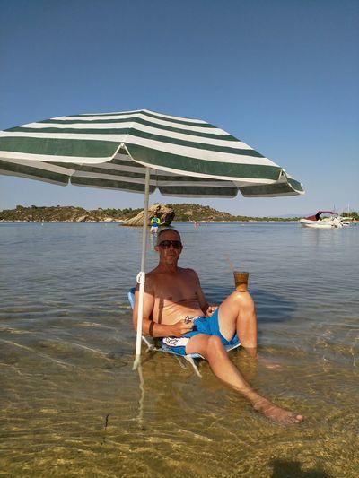 Full length of shirtless man in sea against sky