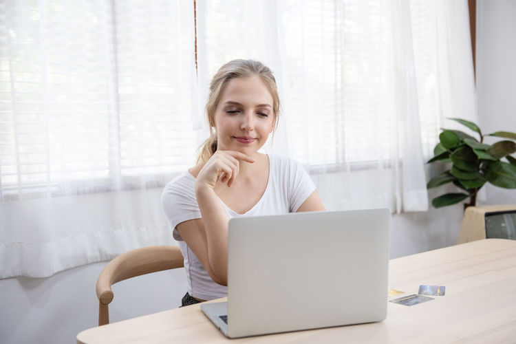 Full length of woman sitting on table at home