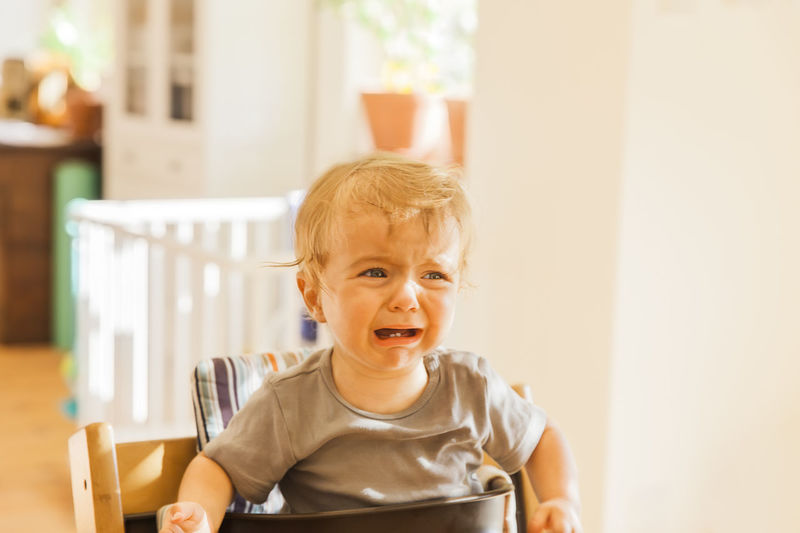 Boy in high chair crying at home