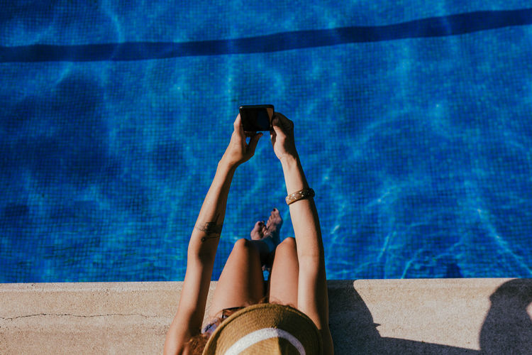 Low section of woman using smart phone at swimming pool