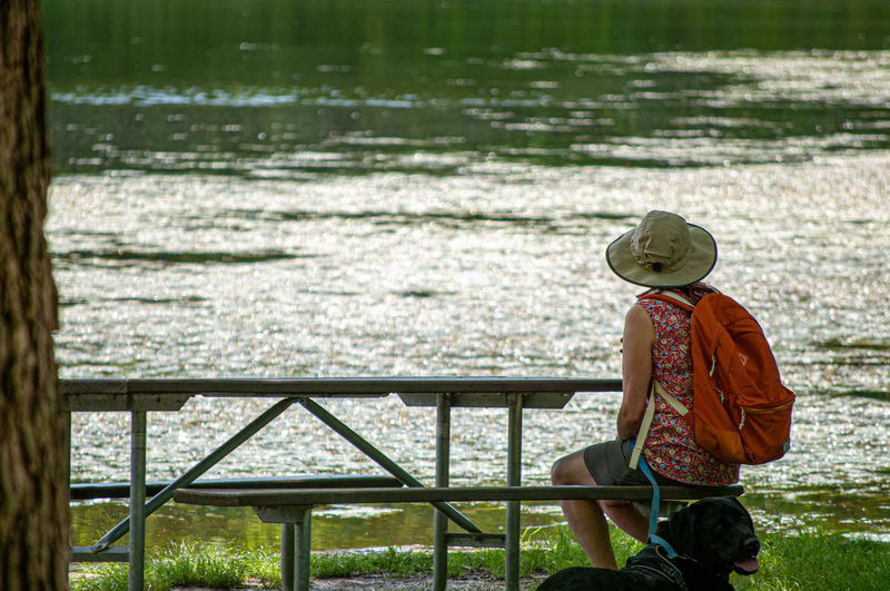 Water Women Sitting Rear View Hat Hiker Scenics Sun Hat Non-urban Scene Tranquility Idyllic Tranquil Scene Calm