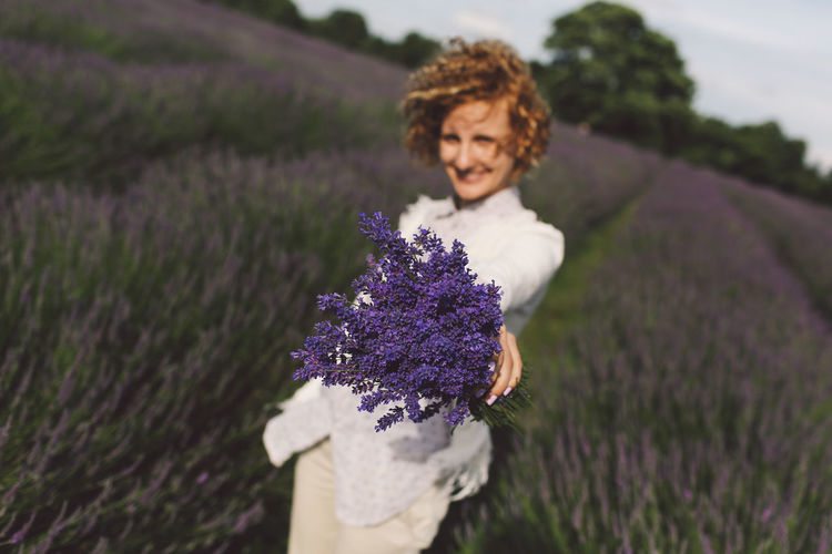 Portrait Of Happy Woman Holding Lavender Bouquet Field