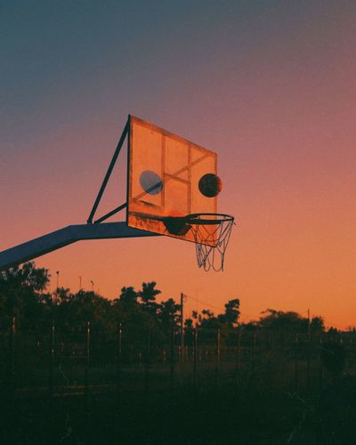Basketball hoop during pink tinted sunset