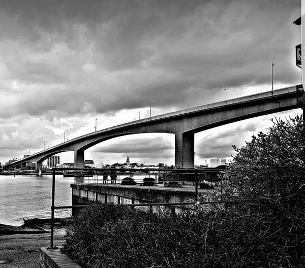 Low Angle View Of Bridge Over River Against Cloudy Sky In City