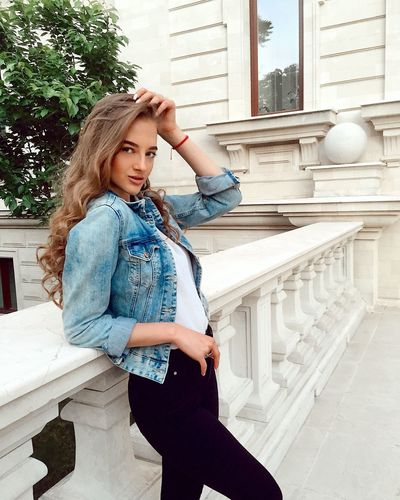 Portrait of beautiful young woman standing by railing