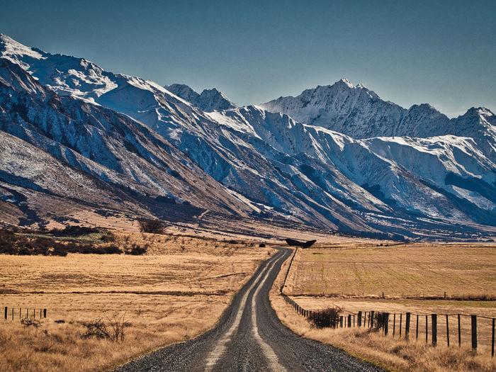 Road amidst landscape against snowcapped mountain