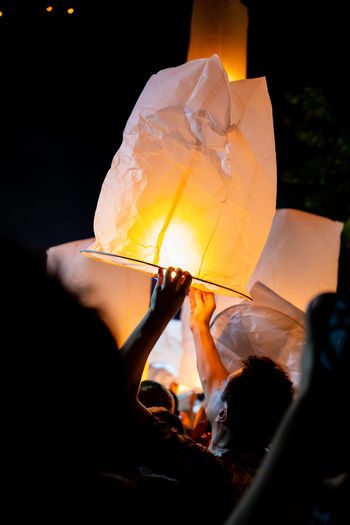 Man releasing illuminated paper lantern at night