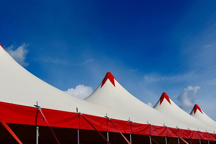 Linkage Bars String Textile Blue Sky Roof Arts Culture And Entertainment Tent Roof Event Circus Tent Tent Circus Sky Nature Day Red Blue Bunting No People Low Angle View Outdoors Cloud - Sky Hanging Multi Colored Built Structure