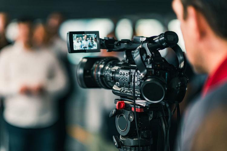 Close-up of cameraman filming in studio