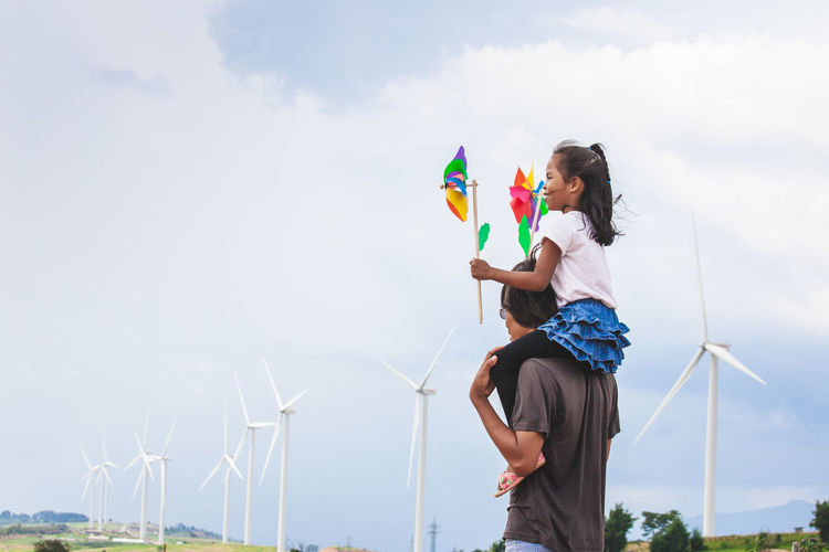 Side view of daughter with pinwheel toys sitting on father shoulders with windmills in background