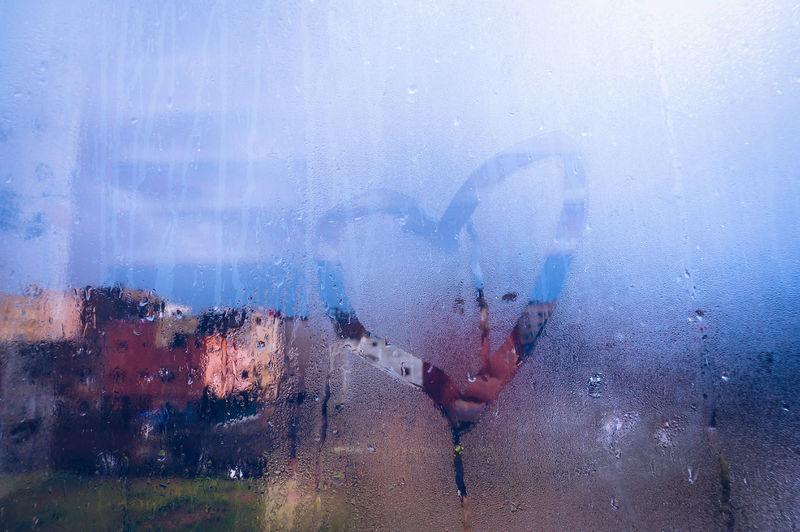 Close-up of heart shape on wet window glass