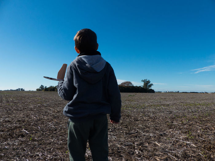 Boy with toy airplane standing on land