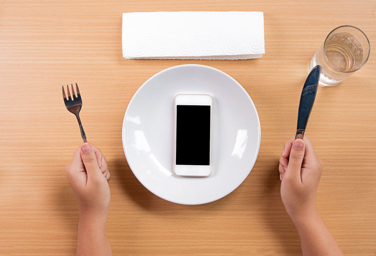 Directly above shot of hand holding fork and butter knife with mobile phone on table