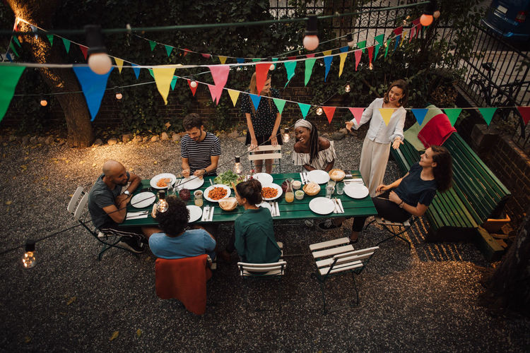 High angle view of multi-ethnic friends enjoying dinner at table during garden party