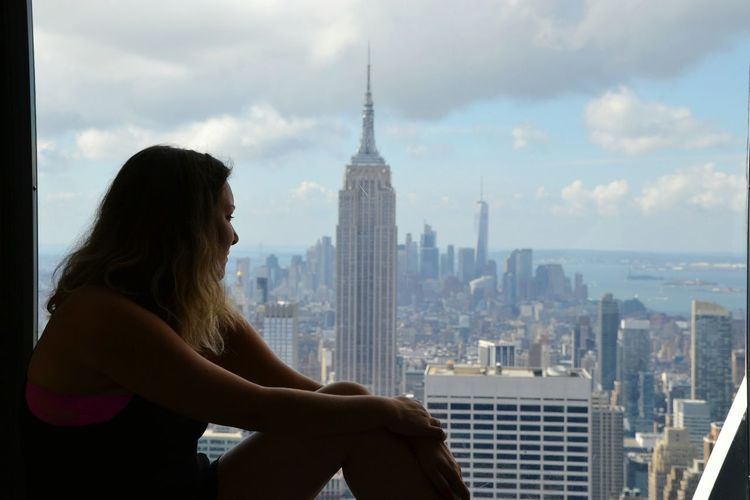 Side view of young woman looking at empire state building in city