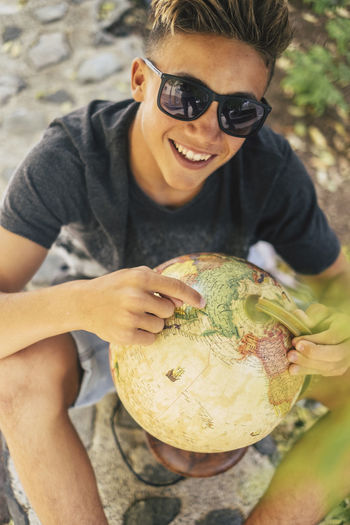High angle portrait of smiling teenage boy holding globe