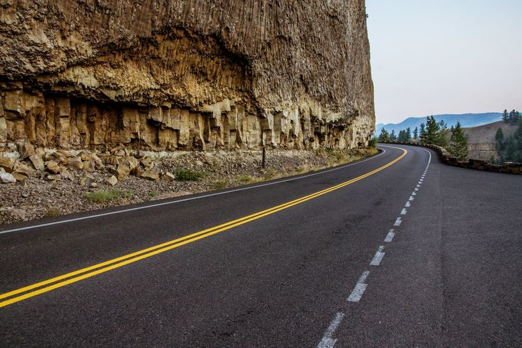 Empty mountain road by cliff