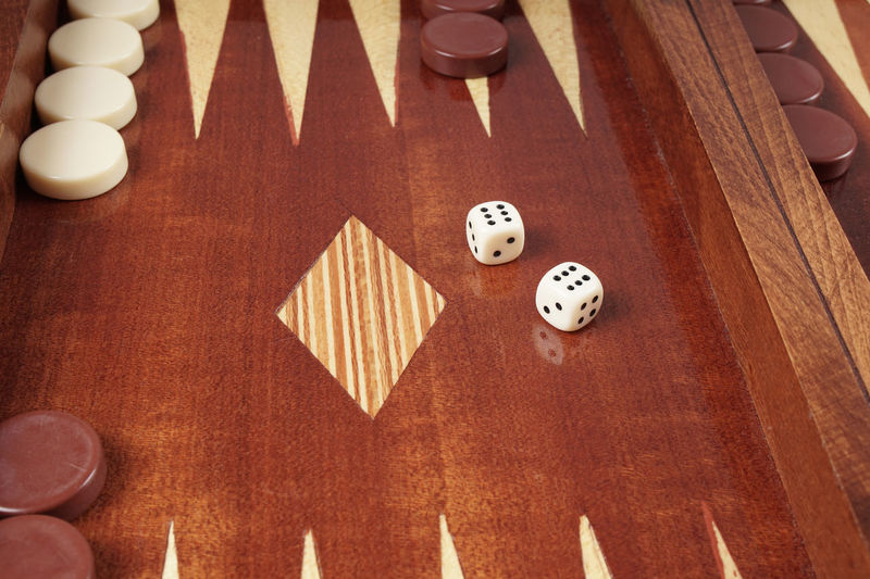 Close-Up Of Rolling Dices On Wooden Table