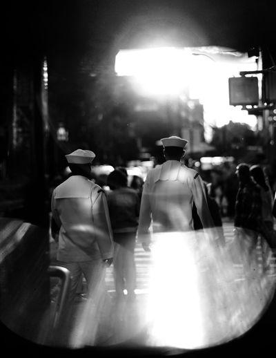People walking on street in illuminated city at night