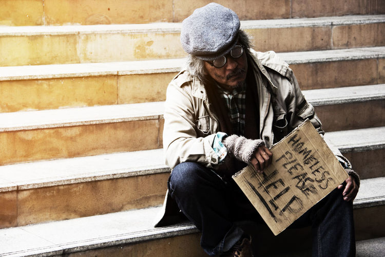 Homeless man holding sign while sitting on steps