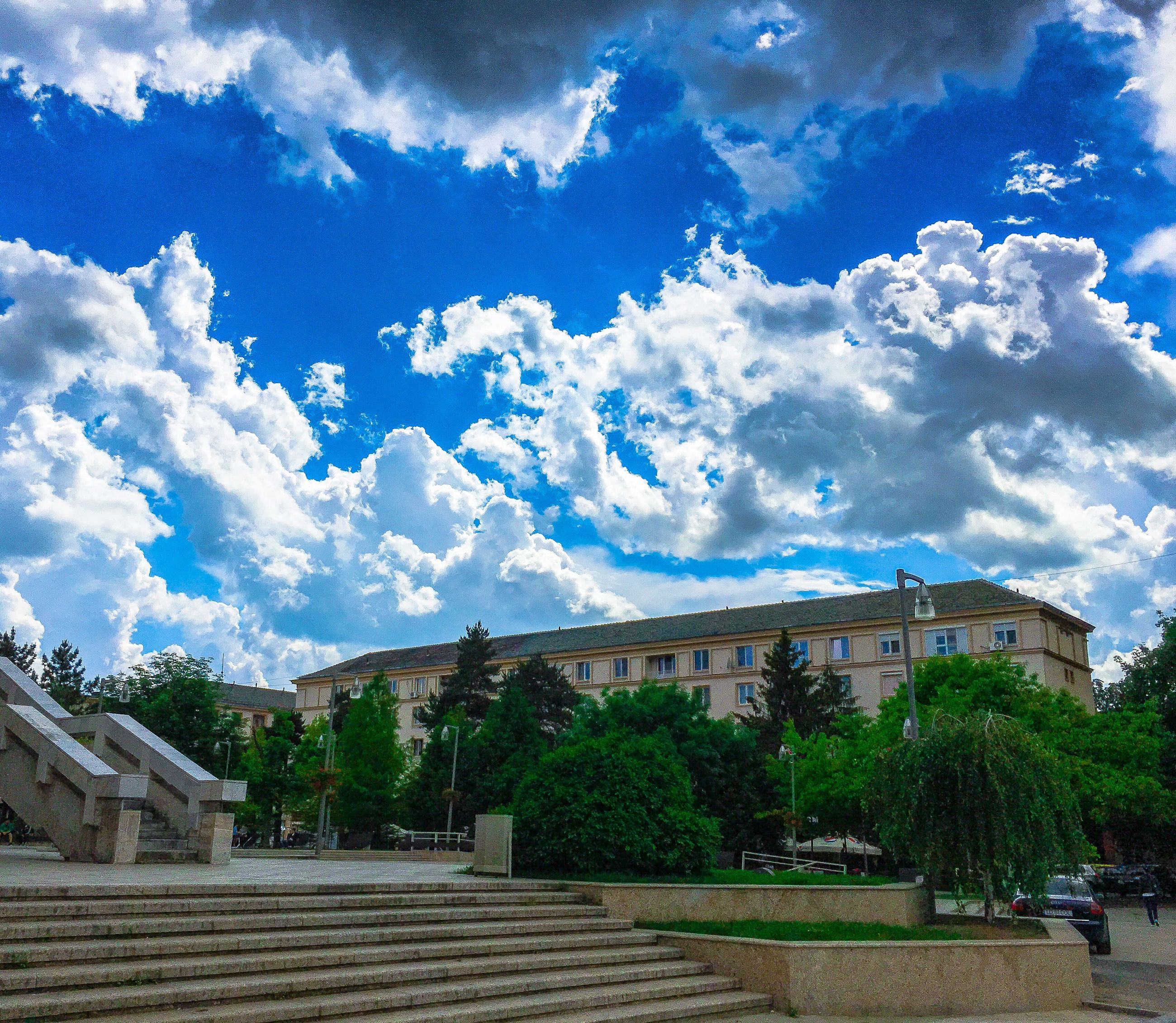 sky, tree, cloud - sky, architecture, built structure, building exterior, cloud, cloudy, day, blue, incidental people, outdoors, railing, transportation, nature, travel, city, low angle view, growth, steps