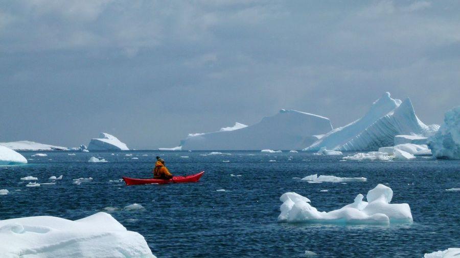 Man kayaking in sea by icebergs against sky