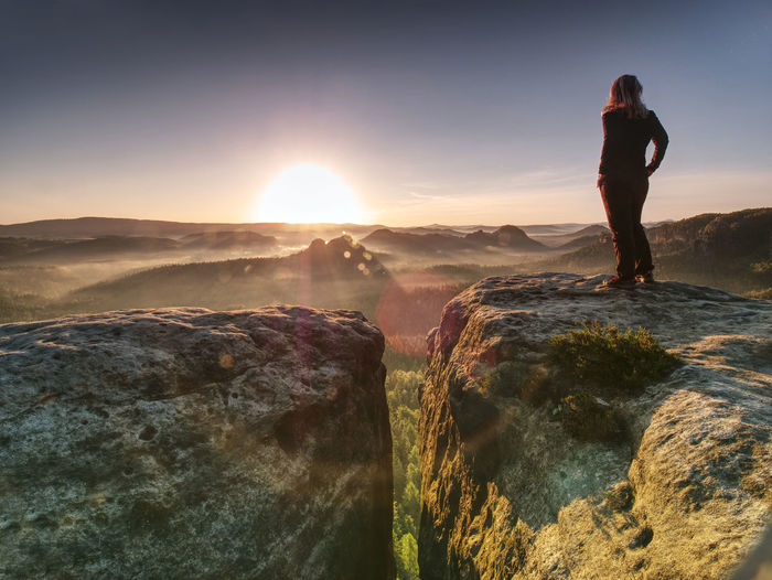 Alone woman hiker model in wild nature within marvelous sunrise. misty valley somewhere in hills
