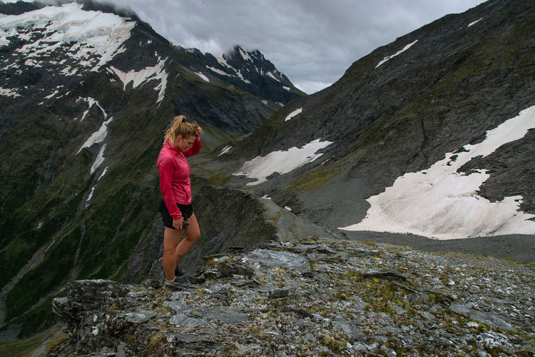 Woman standing on rock against mountains