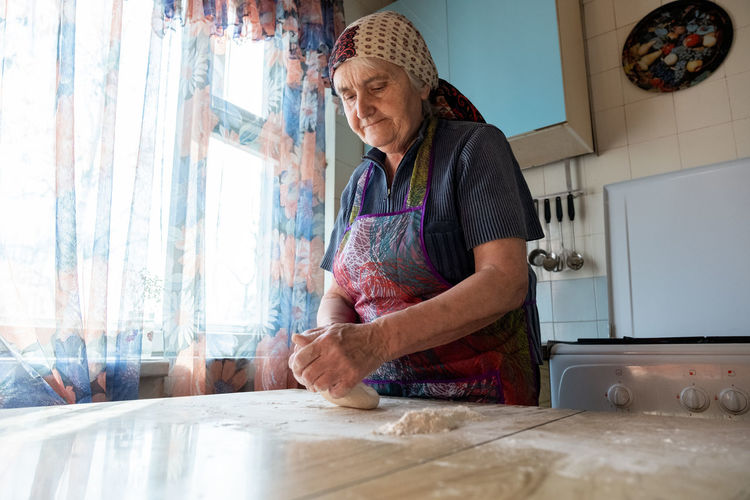 Senior woman kneading the dough in her home kitchen, grandmother cooking bakery products, fresh bread, tasty pie One Person Kitchen Indoors  Real People Preparation  Domestic Room Adult Domestic Kitchen Table Apron Lifestyles Food And Drink Home Interior Food Domestic Life Home Women Casual Clothing Preparing Food Hairstyle Kneading Dough Grandmother Cooking Bakery Bread