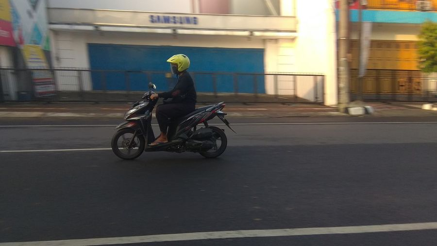 Side view of a person riding bicycle on road