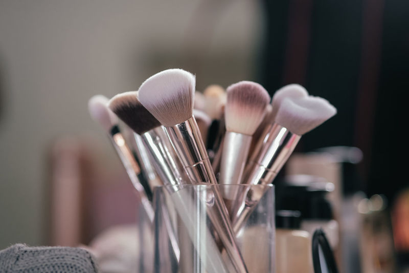 Close-up of make-up brushes in container on table
