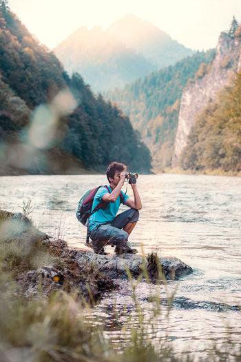 Boy looking through binoculars at riverbank