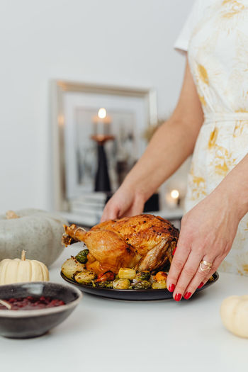 Midsection of woman having food on table at home