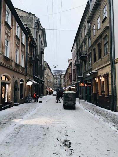 Road amidst buildings in city during winter