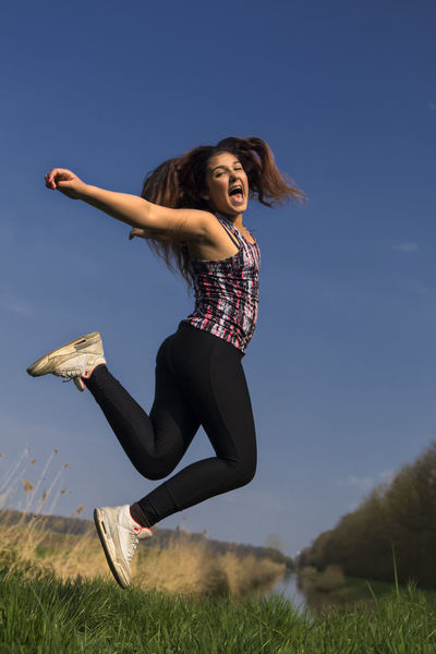 Casual Clothing Day Field Full Length Fun Grass Hairstyle Happiness Human Arm Jump Of Joy Jumping Jumping Girl Land Leisure Activity Lifestyles Nature One Person Outdoors Plant Real People Sky Sporty Girl Young Adult Young Women