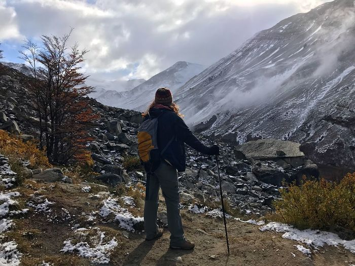 Hiker standing against snowcapped mountains