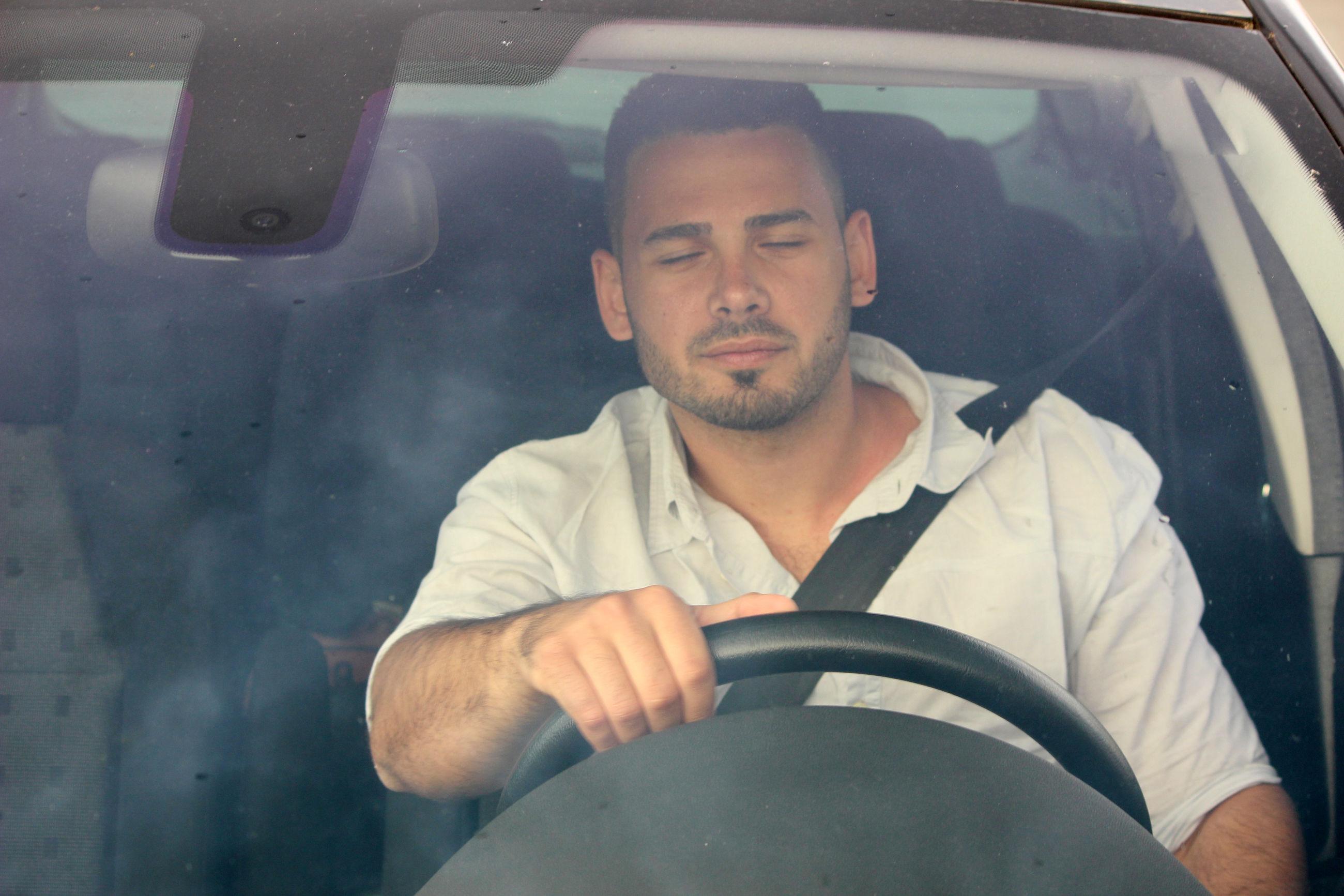 PORTRAIT OF MAN SITTING BY CAR WINDOW