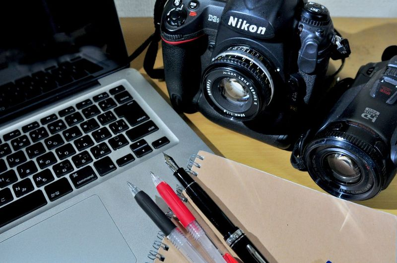 Work Black Color Camera Camera - Photographic Equipment Close-up Communication Computer Connection Digital Camera High Angle View Indoors  Journalism Keyboard Laptop Lens - Optical Instrument No People Pen Photographic Equipment Photography Themes Still Life Table Technology Text Working Equipment