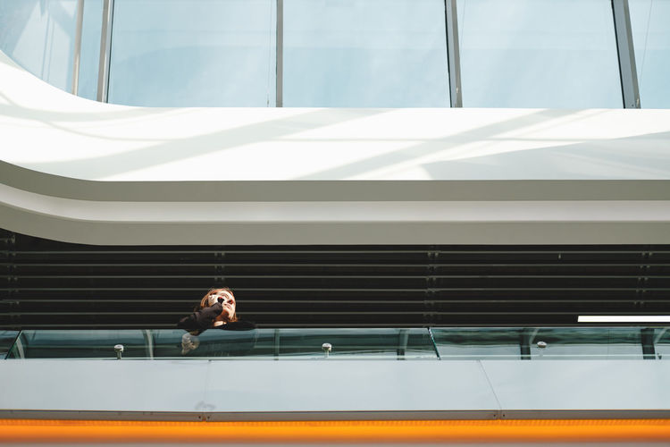 Low angle view of woman talking on phone while standing at balcony