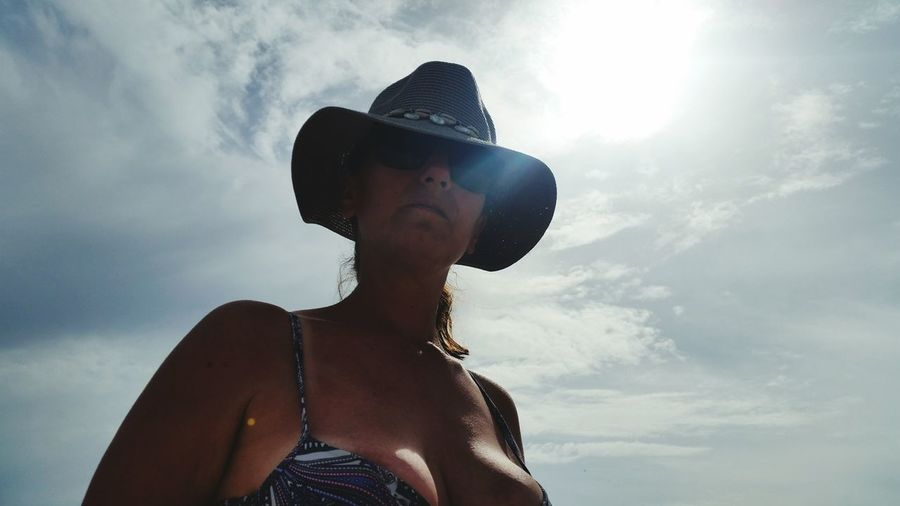 Low angle view of woman wearing hat standing against sky