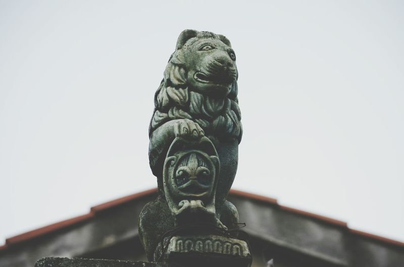 Low angle view of lion sculpture by building against clear sky