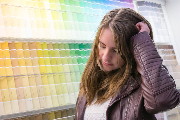 Young woman standing by colorful color swatches at store