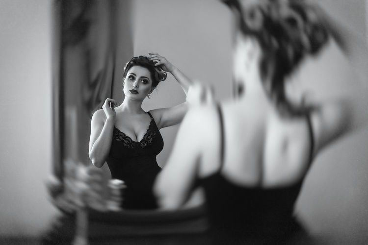 Young woman looking away reflecting in mirror